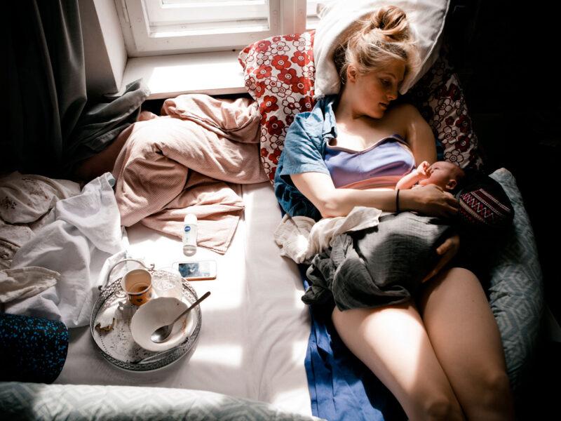 Junge Mama mit Neugeborenem im Wochenbett